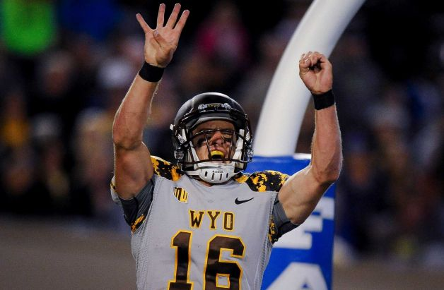 Wyoming quarterback Brett Smith raises the 4-0 after a touchdown scramble vs. Air Force on Saturday night. (Photo courtesy of Michael Ciaglo of The Gazette)