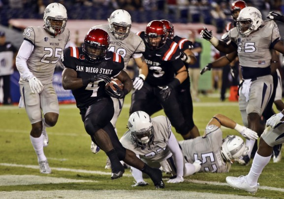San Diego State running back Adam Muema rushes through the Nevada Wolf Pack defense for a gain on Friday night. The Aztecs went on to win in overtime 51-44. (Photo via Lenny Ignelzi of the AP)