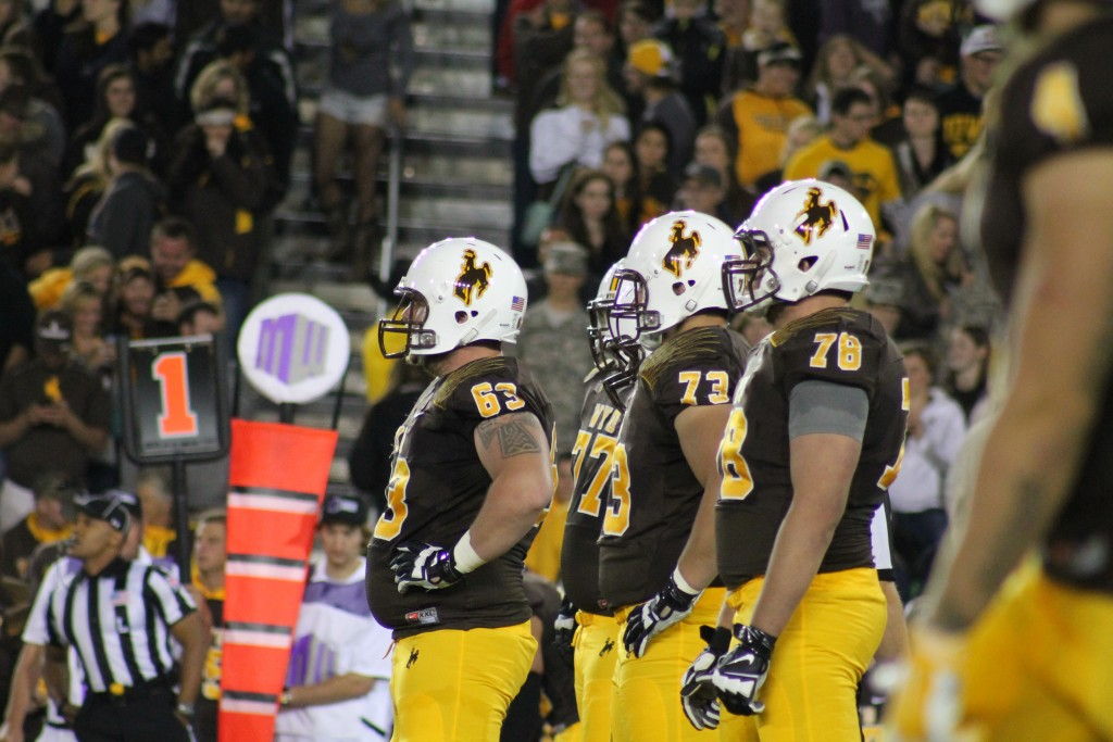 The Wyoming offensive line gets ready pre-snap before in a recent game vs Air Force. (Photo via KFBC Radio)