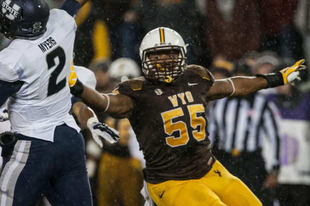 Wyoming defensive end Eddie Yarbrough interrupts the backfield while Utah State's Kent Myers attempts a pass. Yarbrough is a pre-season 1st team All-MW selection. (Photo via Ryan Dorgan/Casper Star Tribune)