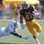 University of Wyoming Shaun Wick runs  by Great Ibe of Eastern Michigan University at Jonah Field at War Memorial Stadium. Wick will return to the Pokes this season after receiving a medical redshirt. (Photo via Michael Smith/UW)